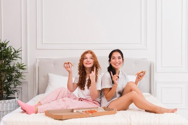 Jeunes femmes mangeant de la pizza au lit