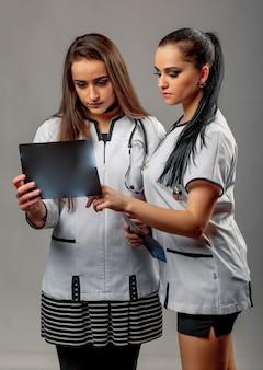 Jeunes femmes médecin attrayant portant une blouse médicale sont debout au studio et à la recherche sur les rayons x.