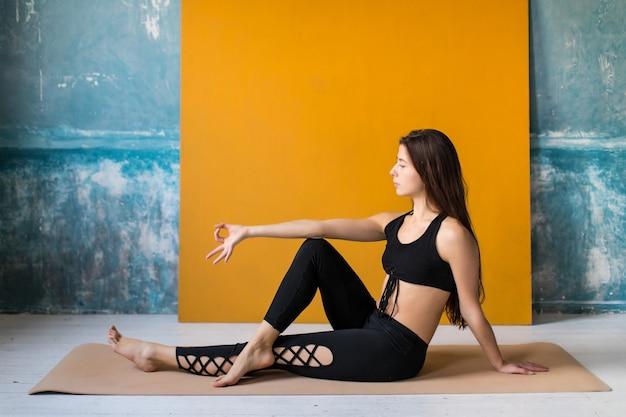 Jeunes femmes méditant avec jnana mudra signe au cours de yoga. elle est assise sur un tapis de fitness avec les jambes croisées. exercice d'étirement de yoga.