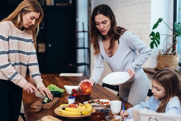 Les jeunes femmes mettent la table, la fille fait ses devoirs.