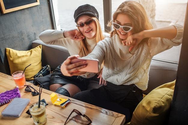 Les jeunes femmes à la mode portent des lunettes de soleil et prennent un selfie. les modèles posent. ils ont l'air fantastiques.