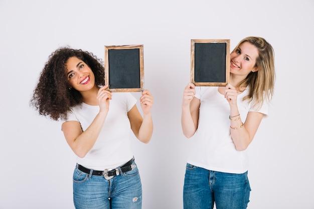 Jeunes femmes montrant des tableaux noirs