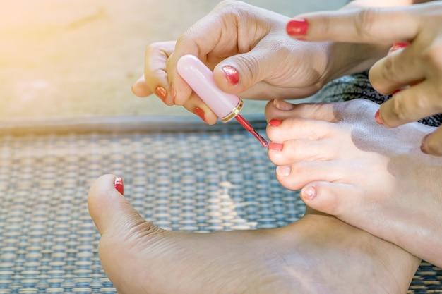 Les jeunes femmes ont des ongles peints avec du vernis à ongles rouge.