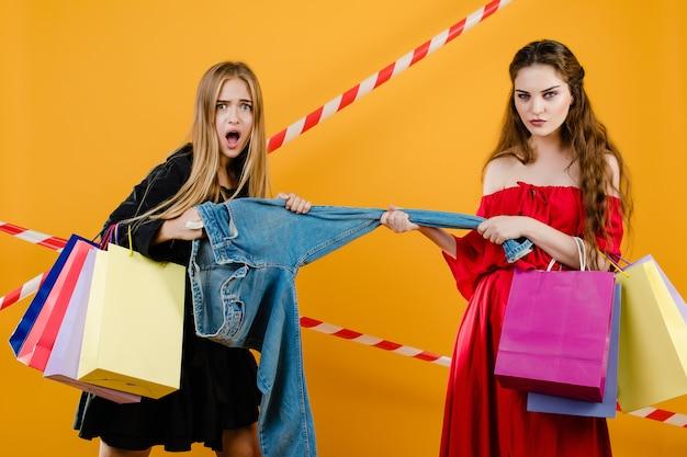 Jeunes femmes portant des robes se disputant une paire de jeans avec des sacs isolés sur jaune