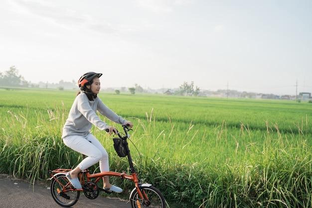 Les Jeunes Femmes Portent Des Casques Pour Faire Du Vélo Pliant Dans Les Rizières Photo Premium