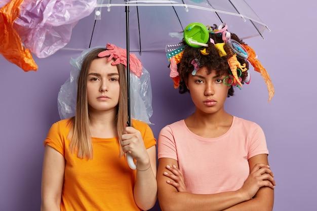 Jeunes femmes posant avec des déchets plastiques