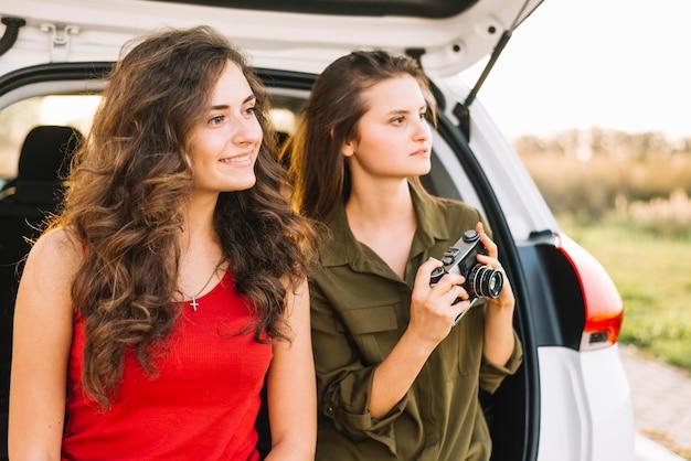 Jeunes femmes prenant des photos près de la voiture