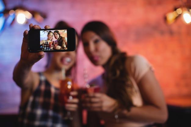 Jeunes femmes prenant un selfie tout en prenant des cocktails