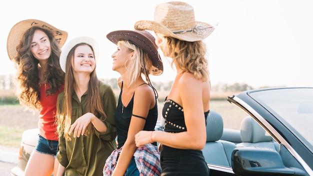Jeunes femmes près de cabriolet noir