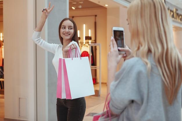 Jeunes femmes profitant du shopping ensemble au centre commercial