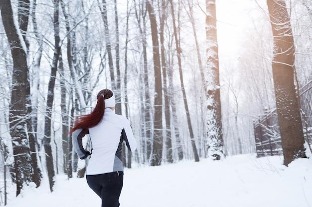 Jeunes femmes qui courent dans la forêt d'hiver