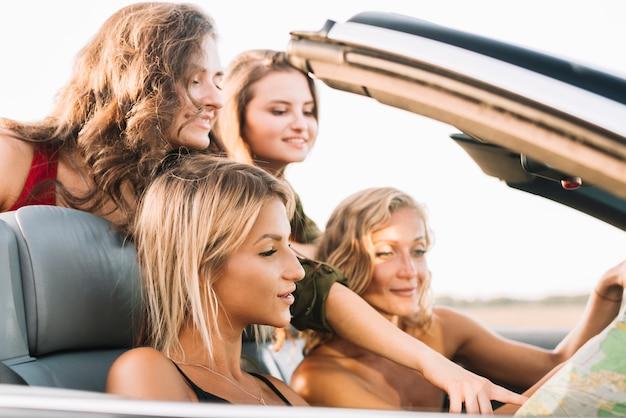 Jeunes femmes regardant la carte en voiture