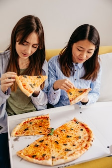 Jeunes femmes relaxantes, manger des pizzas