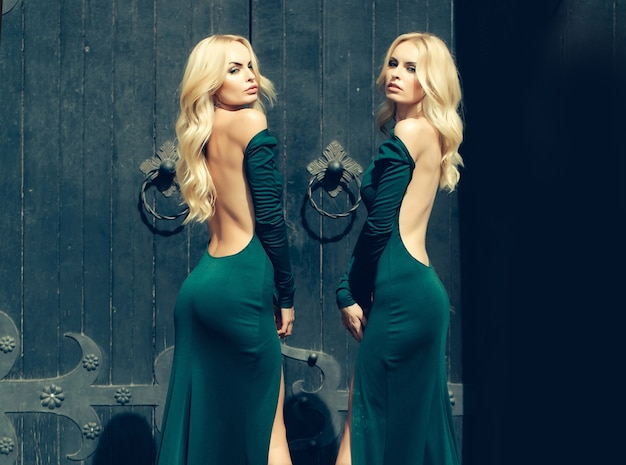 Les jeunes femmes en robe de mode debout près de la grande porte