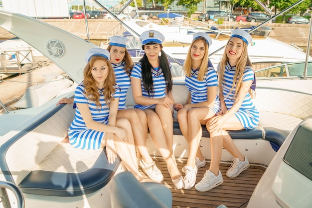 Les jeunes femmes en robes rayées et casquettes, sur le pont d'un yacht, le concept de loisirs sur un yacht.