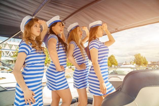 Jeunes femmes en robes rayées et casquettes, sur le pont d'un yacht