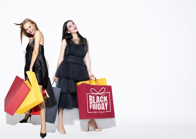 Jeunes femmes en robes shopping sur fond blanc. modèles féminins caucasiens attrayants. finances, vendredi noir, cyber lundi, ventes, concept d'automne. espace de copie. souriant, posant heureux.