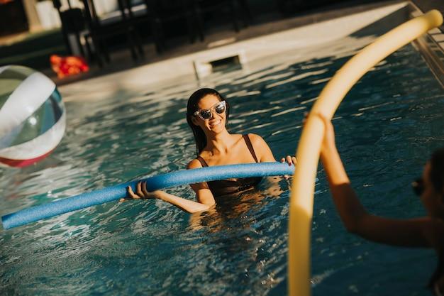 Jeunes femmes s'amusant avec des nouilles de piscine