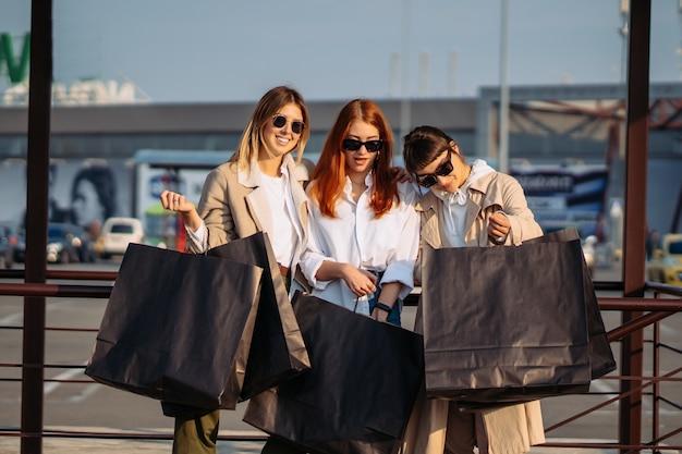 Jeunes femmes avec des sacs à provisions sur un arrêt de bus