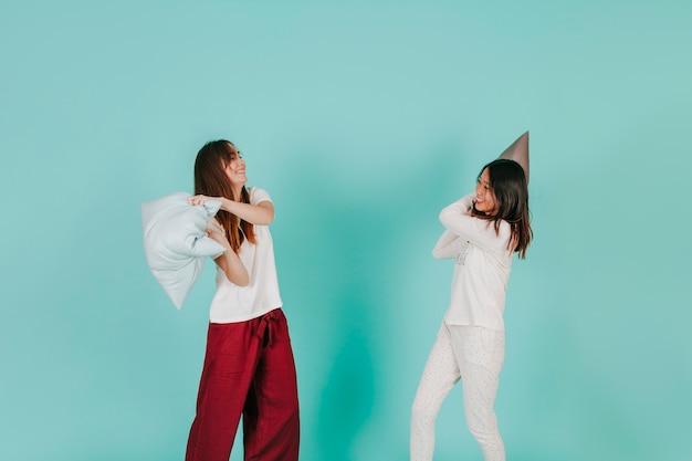 Jeunes femmes se battant avec des oreillers