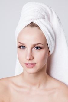 Jeunes femmes avec une serviette sur la tête en regardant la caméra. intérieur. soin de la peau