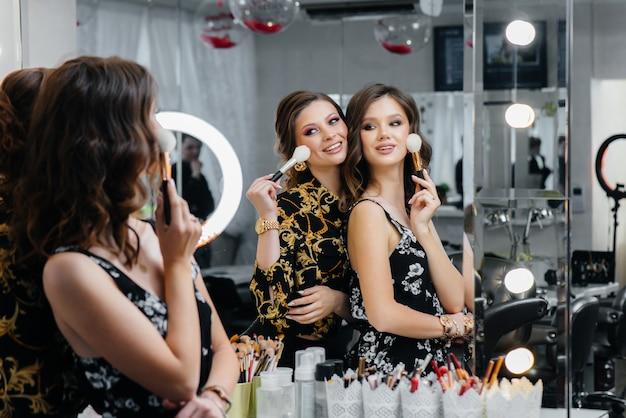 De jeunes femmes sexy s'amusent et se maquillent pour faire la fête devant le miroir