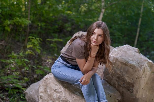 Les jeunes femmes sont assises sur des kilomètres dans une forêt entourée d'arbres verts. paix et calme dans le regard.