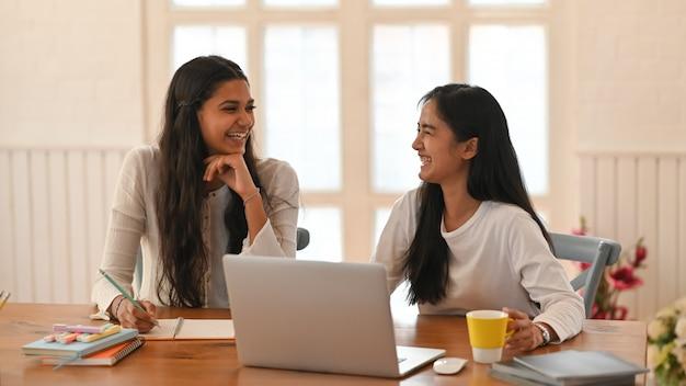 Les jeunes femmes sont assises et souriant à la table en bois entourée d'un ordinateur portable et de l'équipement