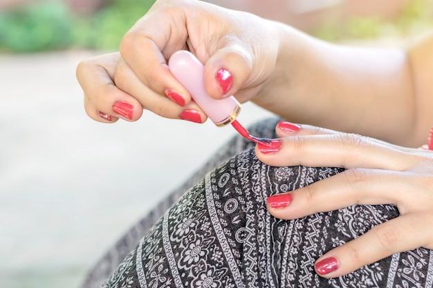 Les jeunes femmes sont peintes ongle avec vernis à ongles rouge.
