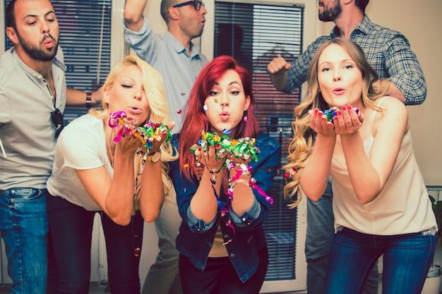 Des jeunes femmes soufflent des confettis à la fête