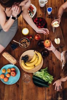 Jeunes femmes sportives à la table de la cuisine avec fruits et légumes.
