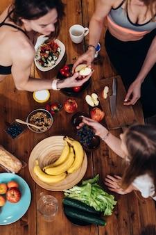 Jeunes femmes en tenue de sport mangeant des pommes, des raisins dans la cuisine.