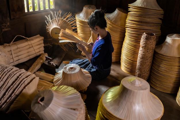 Les jeunes femmes tissent dans le panier fait main de champ de la thaïlande.