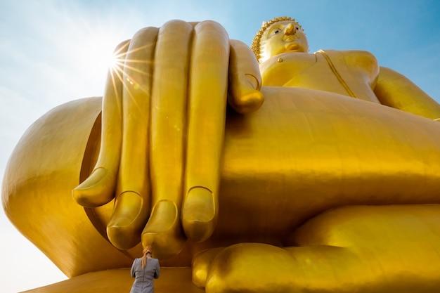 Les jeunes femmes touristes rendent hommage aux doigts du grand bouddha d'or en thaïlande