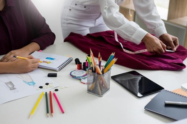 Jeunes femmes travaillant comme créateurs de mode et croquis