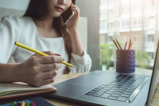 Jeunes femmes travaillant avec un crayon de couleur et un cahier