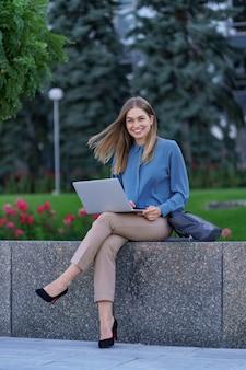 Jeunes femmes travaillant sur ordinateur portable sur la place de la ville