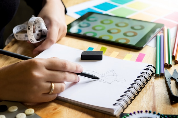Jeunes femmes travaillant en tant que styliste dessiner des croquis pour les vêtements dans l'atelier