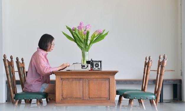 Les jeunes femmes utilisent de vieilles machines à écrire dans le bureau classique.