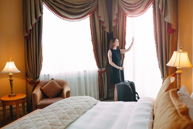 Jeunes femmes avec valise séjournent dans une chambre d'hôtel