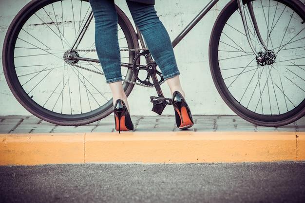 Les jeunes femmes et un vélo en face de la ville