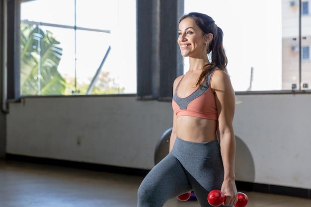 Jeunes femmes en vêtements de sport faire des exercices avec des haltères dans la salle de gym.