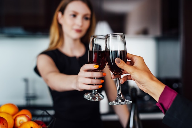 Jeunes femmes vêtues d'une élégante robe noire tenant une bouteille de vin rouge et un verre debout au bar de la cuisine en regardant son amie.