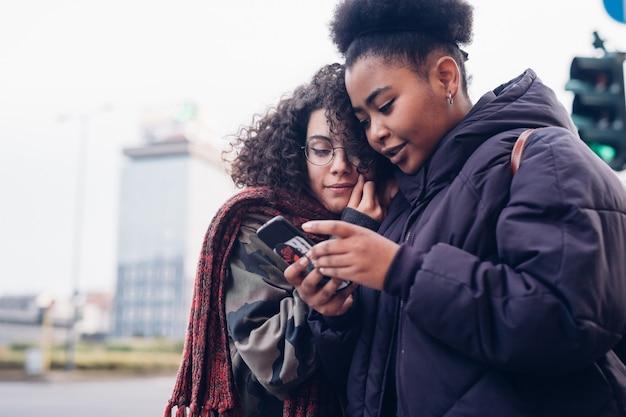 Jeunes filles à l'aide de smartphone dans la ville