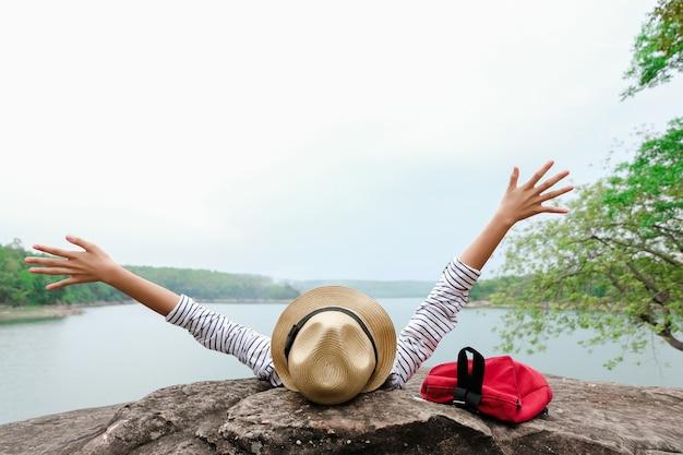 Jeunes filles asiatiques avec sac à dos lumineux en appréciant dans la nature pendant les vacances.