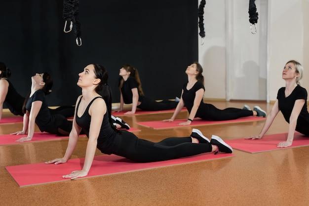 Les jeunes filles athlétiques s'échauffent avant de s'entraîner dans la salle de sport