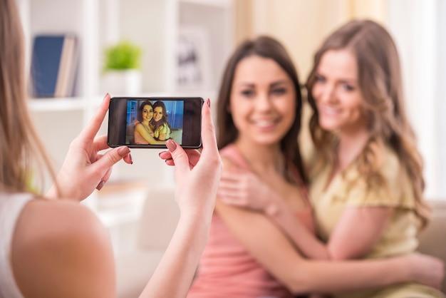 Les jeunes filles de beauté prennent une photo à la maison.