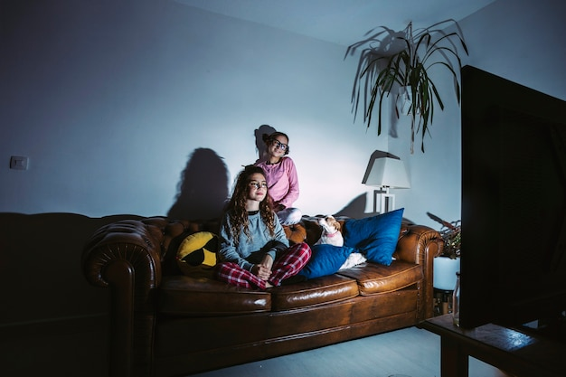 Jeunes filles avec un chien qui regarde la télé