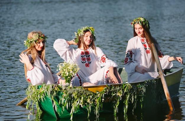 Des jeunes filles en costumes nationaux naviguent dans un bateau orné de feuilles et de phanères. fête slave d'ivan kupala.