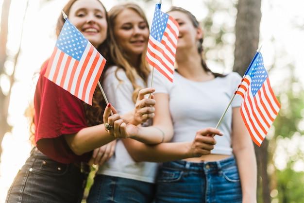 Jeunes filles dans la nature avec des drapeaux américains